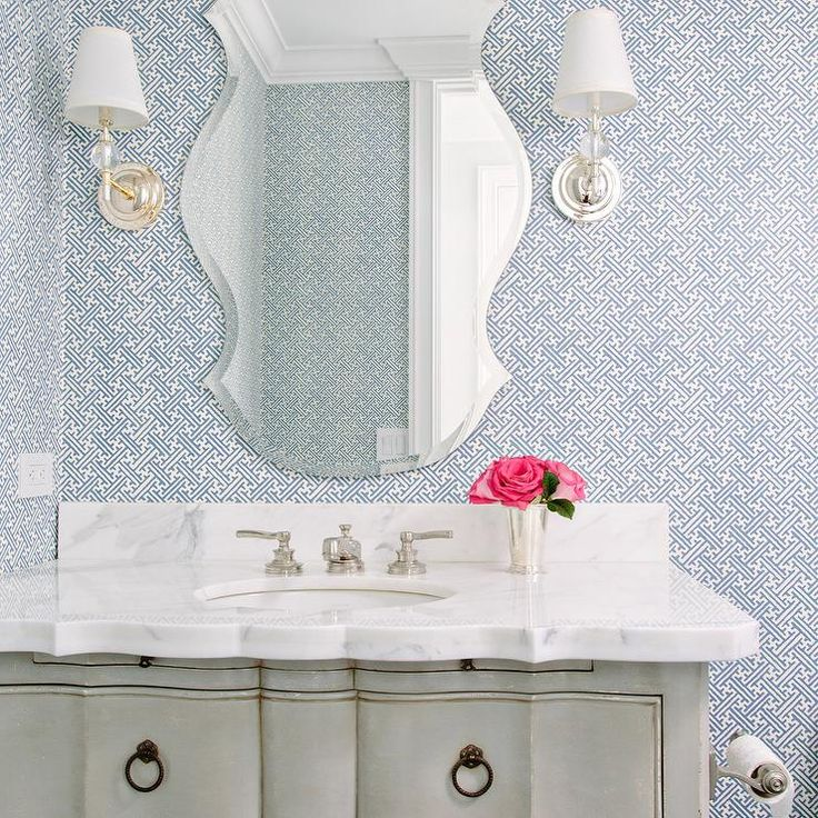 Blue and gray powder room features walls clad in blue maze wallpaper, Campbell Hydrangea Wallpaper, lined with a gray French vanity adorned with ring pulls topped with a scalloped marble countertop under a curved beveled frameless mirror and Robert Abbey The Muses 1 Light Wall Sconces in Crystal.