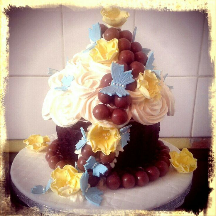 Giant chocolate cupcake with maltesers, yellow flowers and blue butterflies