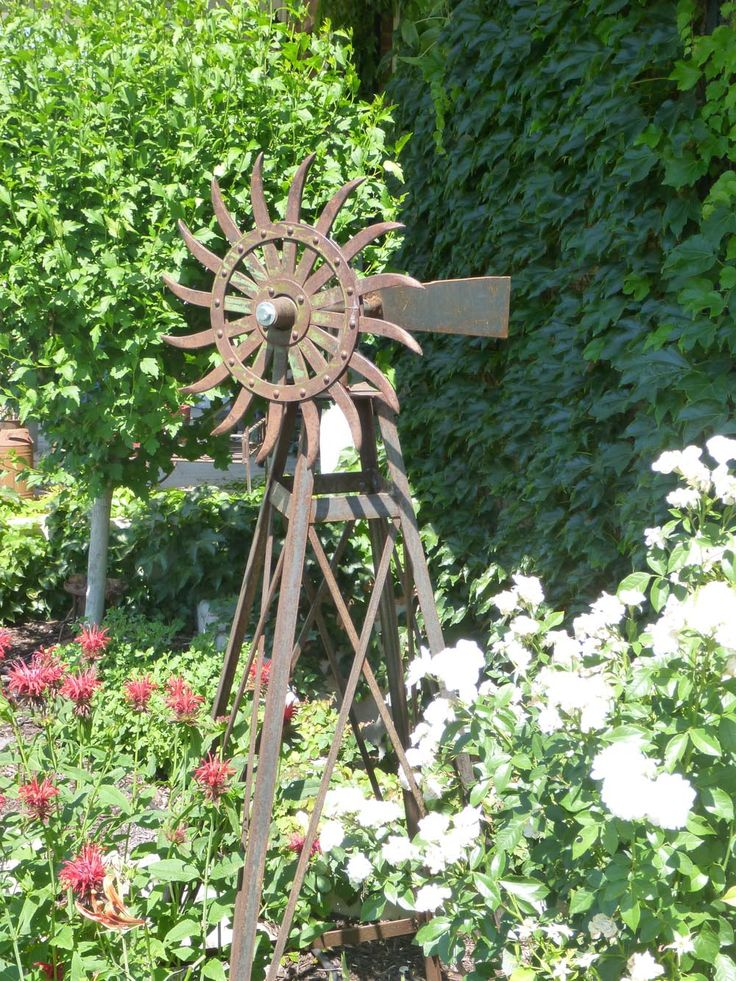 RUSTIC Utah Item #26: Decorative windmill for use as yard art. Legs make great trellis for climbing plants. Head made from antique rotary hoe wheel.
