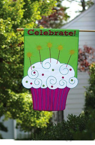 """Celebrate Cupcake Flag (Regular Size) by Evergreen. Save 43 Off!. $22.70. Applique Flag. Shimmer Accents. 28"""" x 44"""". A flag is the greeting card of your home. Great for yourself or as a gift. Sprinkles cover this cupcake's frosting like confetti as candles burn brightly ready to grant a birthday wish. Luscious white frosting stands out above a pink and purple striped wrapper and a green background. It declares, """"Celebrate!"""" with festive charm, waving in the wind in colorful glory."""
