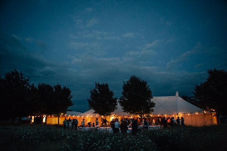 Traditional Canvas Pole Tent by night with festoon lighting.