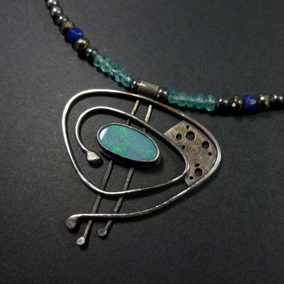 Este anuncio es una versión de un colgante de ópalo bueno, hecho a mano - es verdaderamente cósmico y fue inspirado por el mágicos espirales de las galaxias.  Cuenta con un doblete de ópalo australiano 16x8mm hipnotizantes. Un doblete es un trozo de ópalo fijada a una pieza más fuerte de la piedra para la estabilidad. Este es un color azul cielo con destellos de neón verde. Para complementar estos colores he formado el colgante con perlas facetadas en apatita, Pirita y Lapis. Estos granos…