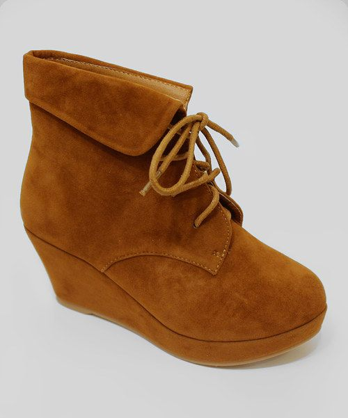 Elevate any outfit to high fashion with these height-boosting wedge booties. With a classic lace-up front and folded cuff, this pair offers a smart look that adds stylish sophistication to any ensemble. 2.25'' heel with 5'' platform4.75'' shaft9.5'' circumferenceSample size Toddler 13Lace-upMan-madeImported