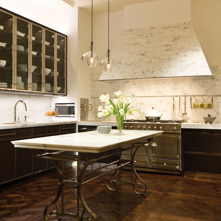 Love that patchwork HB floor, great center island table and glass fronted cabinetry.