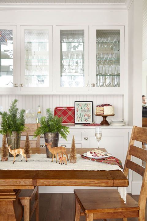 Loose sprigs of greenery in sap buckets, toy deer, and bottlebrush trees create a playfully whimsical tablescape.