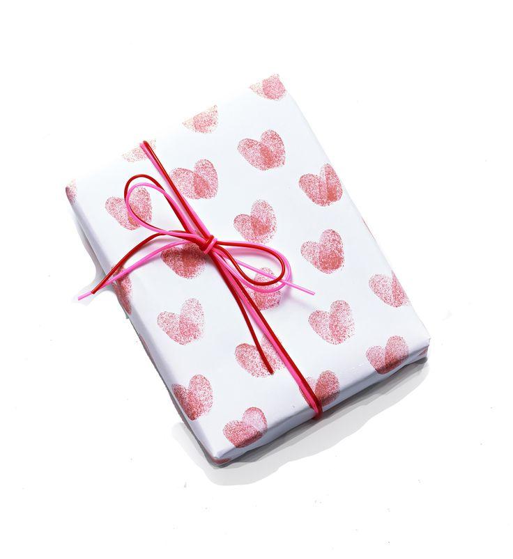 Pakpapier met hartjes gemaakt van duimafdrukken. Vinger op een inktkussentje, één afdruk naar links, één afdruk naar rechts = hartje!