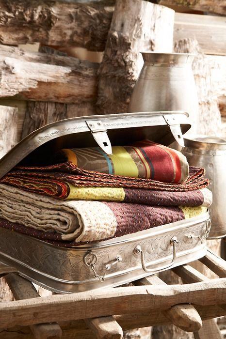 Canasto, valija o cajon con manteles junto a consola