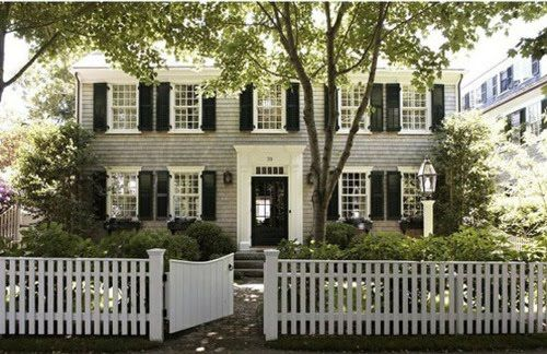 Center hall colonial with black shutters and a picket fence