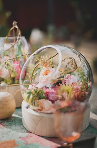 glass bowls filled with pretty petals for an unexpected and sweet centerpiece / http://www.deerpearlflowers.com/20-unique-rustic-terrarium-wedding-centerpieces/