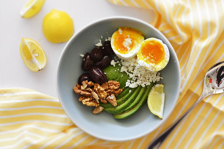 avocado bowl with soft-boiled egg, walnuts, feta cheese and olives