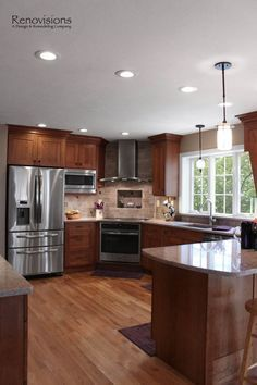 Kitchen remodel by Renovisions. Induction cooktop, stainless steel appliances, cherry cabinets, shaker cabinets, under cabinet lights, tuscan-clay-look porcelain tile backsplash, quartz countertop, peninsula, hardwood flooring, pendant lights, recessed lights, corner stove.: