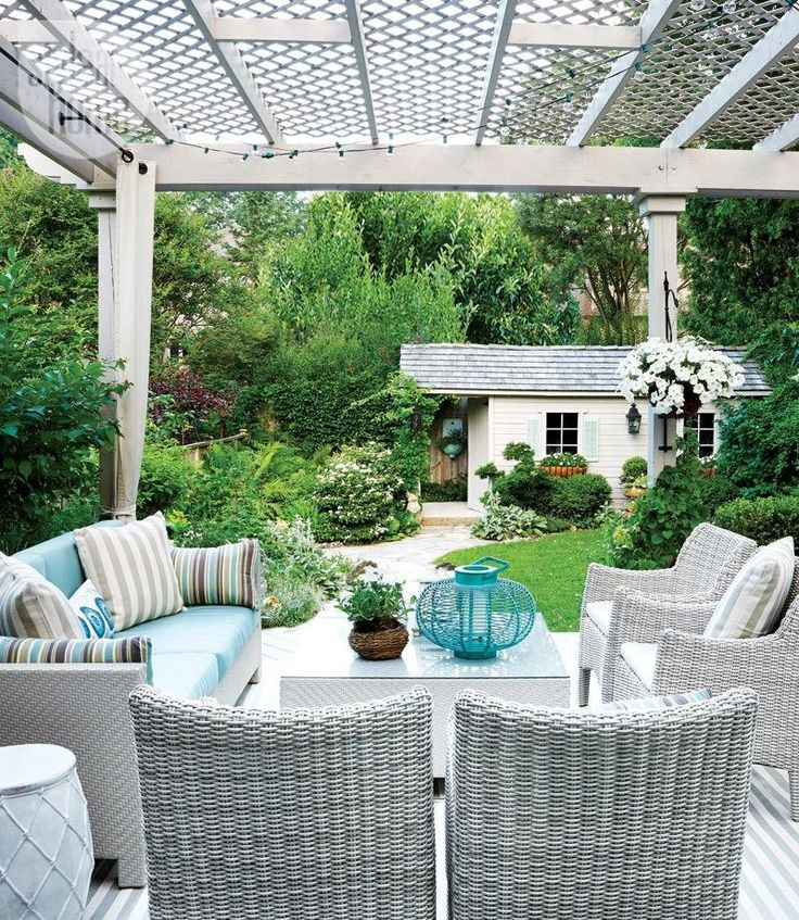 """Grey resin wicker furniture stands up to harsh Canadian weather conditions, and is sturdy and stylish. """"I deliberately included lots of seating so that when we have guests there's a comfortable spot for everyone,"""" says homeowner and Style at Home contributing design editor Christine Hanlon. The deck, pergola and shed were stained in an opaque grey to create a unified scheme."""