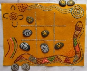 "Australia: Teach kids aboriginal art symbols, and have kids paint aboriginal art symbols on a set of stones to use to play tic tac toe (also called ""ngaka ngaka"", which means ""look look"")."
