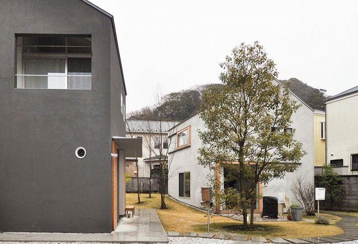 2軒の家が広い敷地に位置をずらして立つ。右がM邸。グレー系の外観の中で気のフレームが際立つ。