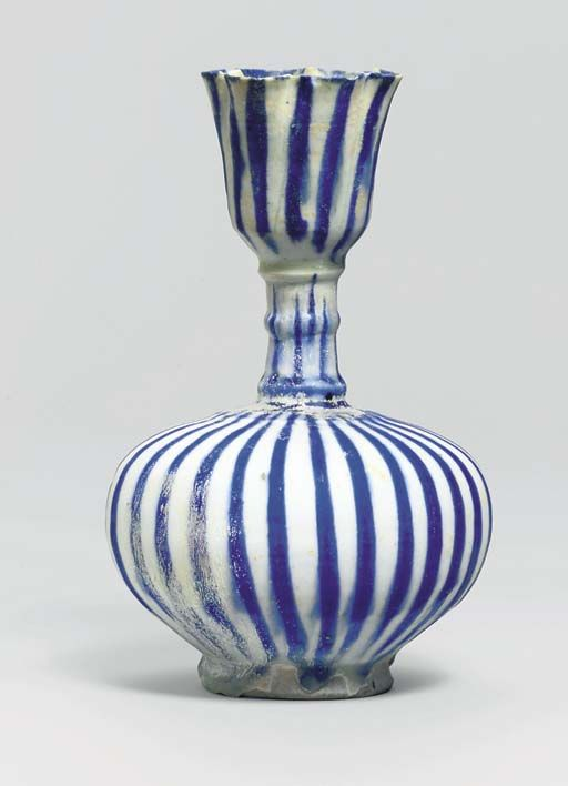 A KASHAN BLUE AND WHITE POTTERY BOTTLE  CENTRAL IRAN, LATE 12TH CENTURY  The spherical body on spreading foot rising to a tubular neck with deep cup-shaped mouth with flaring cusped rim, the surface simply decorated with vertical bright blue stripes, areas of light silvery iridescence on body, light creamy accretions on neck and mouth, composite from two original contemporaneous vessels  9¼in. (23.8cm.) high