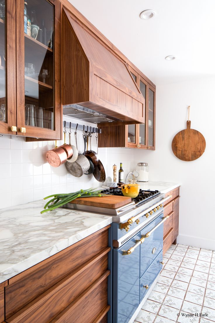 Beautifully updated Tudor kitchen with custom walnut cabinets and Lacanche range. Counters are calacatta marble, Tabarka hand-painted tiles are on th floors, and the star is the Lacanche Saulieu range in Armor. We love the hanging pots, too!  Design by Distinctive Kitchens Seattle