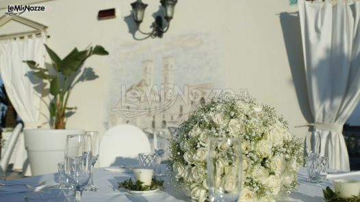 http://www.lemienozze.it/operatori-matrimonio/luoghi_per_il_ricevimento/new-lions-ricevimenti/media/foto/13 Allestimento in bianco e avorio con centrotavola di rose fresche e candele.
