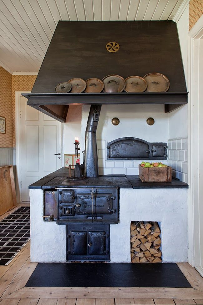 Vedspis | Black, white + brown kitchen with antique oven + storage for pots + pans