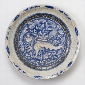 DISH  POT1649    Safavid dish, painted in cobalt blue and black under a transparent glaze. The Buddhist lion in reserve on a ground of dense foliage and cloud scrolls is characteristic of the Chinese Kraakporselein exported for the European market. The cavetto bears a Persian quatrain incised in black slip advising the owner to be content with the worldly goods he has.    Iran late 17th century AD   6.5 x 33 cm (diameter)