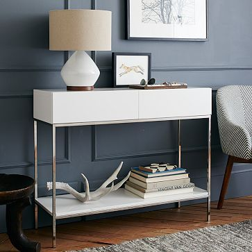 "Lacquer Storage Console: White high-gloss lacquer finish. Stainless steel legs in Polished Nickel. Two drawers open on wooden glides42""w x 14""d x 34""h. $499"
