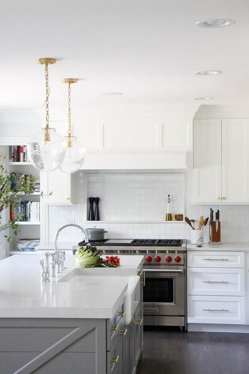 White and gray kitchen boasts a dual Wolf range positioned between white shaker cabinets adorning nickel pulls and a white quartz countertop.