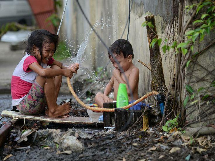 Zaterdag 7 december 2013: Filipijnse kinderen spelen met een waterslang in Tacloban, waar vorige maand een orkaan aan veel mensen het leven heeft gekost.