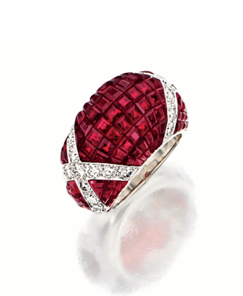 MYSTERY-SET RUBY AND DIAMOND RING, VAN CLEEF & ARPELS, PARIS, VAN CLEEF & ARPELS.  Of tapering bombé form, mystery-set with calibré-cut rubies, the sides decorated with loops of brilliant-cut diamonds, mounted in platinum, signed and numbered M39556, maker's marks, assay marks.