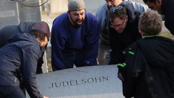 FILE PHOTO: Man shouts as he helps lift a fallen tombstone at the Jewish Mount Carmel Cemetery, February 26, 2017, in Philadelphia, PA.  - Photo:DOMINICK REUTER/AFP