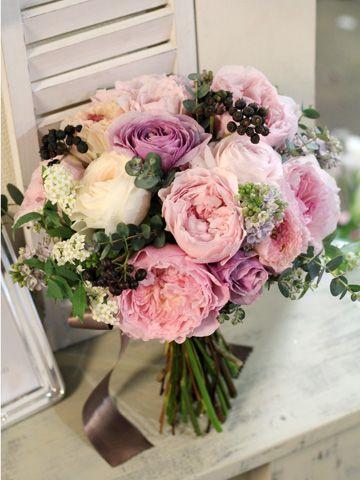 淡いピンクとパープルのバラにライラックやシックなグリーンを合わせた大人っぽいクラッチブーケ。