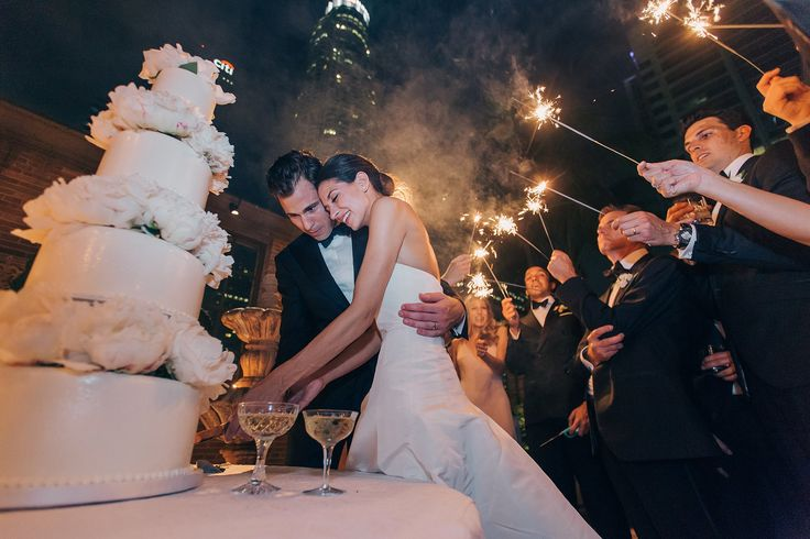 Our wedding party held sparklers as we cut the cake under the downtown skyline of Los Angeles. The building lit up in the back is actually where my office is!