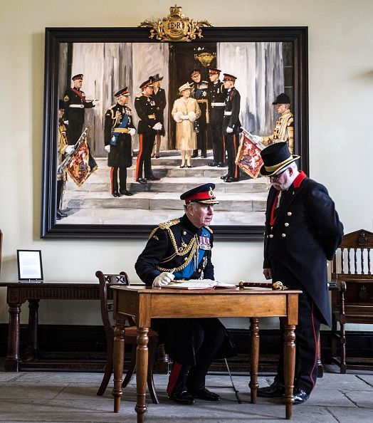 Prince Charles, Prince of Wales signs the visitor book of Sandhurst military academy in front of a giant painting from the time both his sons were attending the academy during the Sovereign's Parade at Royal Military Academy Sandhurst on December 11, 2015 in Camberley, England.