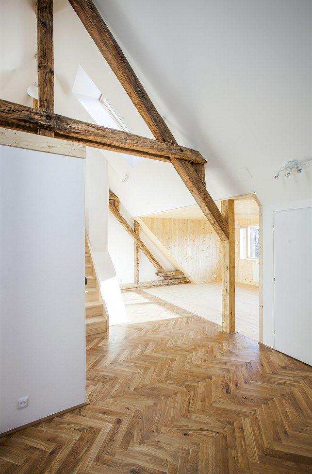 Původní krokve s originálními stopami stáří skvěle korespondují s bělostnou čistotou stěn a nachází svůj analogický odraz v dřevěné vlisové podlaze i v dřevěném obložení. Dostavěná část je jasně vymezena i na podlaze přechodem mezi vlisy a prkny.