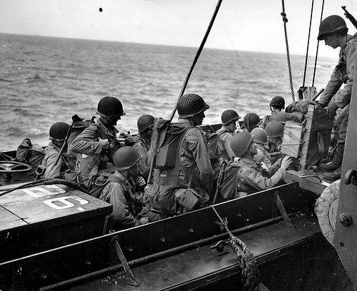 Une unité d'assaut achève d'embarquer à bord d'une barge. Beaucoup de GI's portent le gilet d'assaut caractéristique du D-Day.