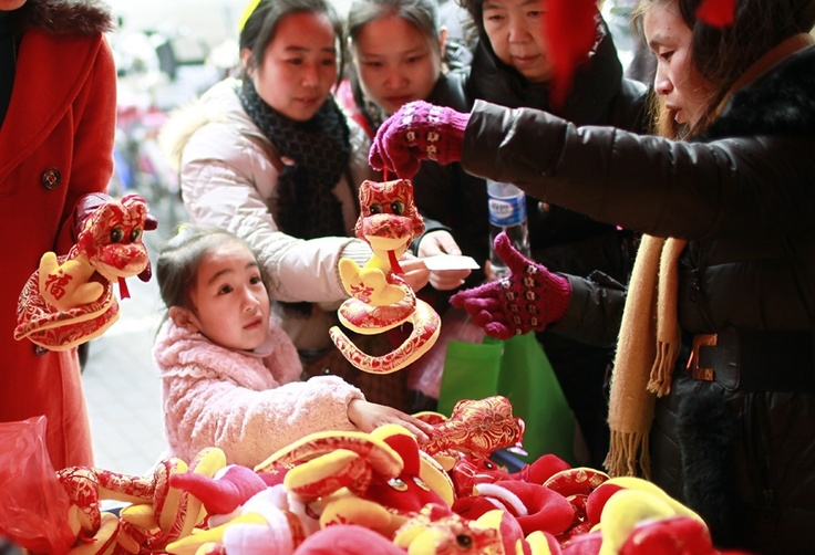 People buy plush toys depicting water snakes in Shanghai ahead of Lunar New Year celebrations