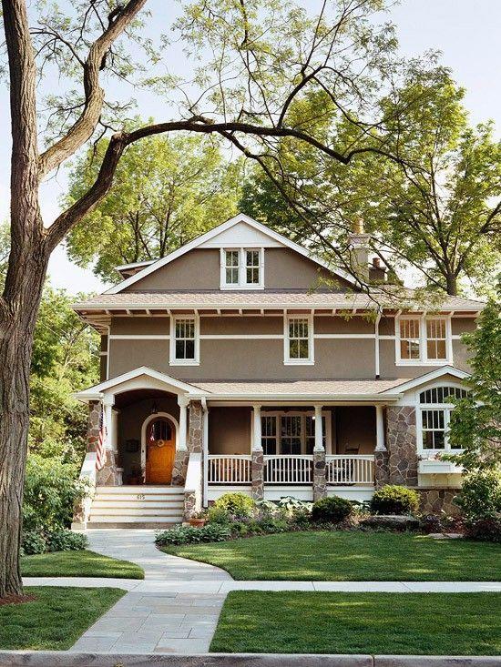 craftsman house stone pillars white trim golden wood