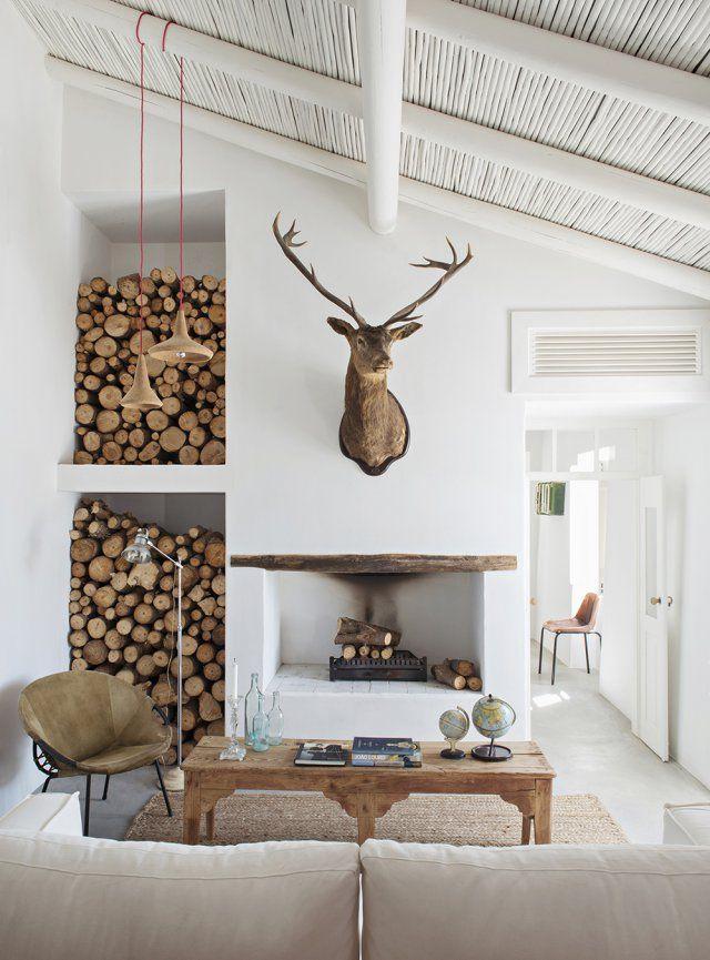 Un séjour à la ferme en mode vintage. Dans le salon, table portugaise en pin du XIXe siècle et cheminée réalisée par l'atelier Rua. Trophée de cerf de la Quinta Infantado.