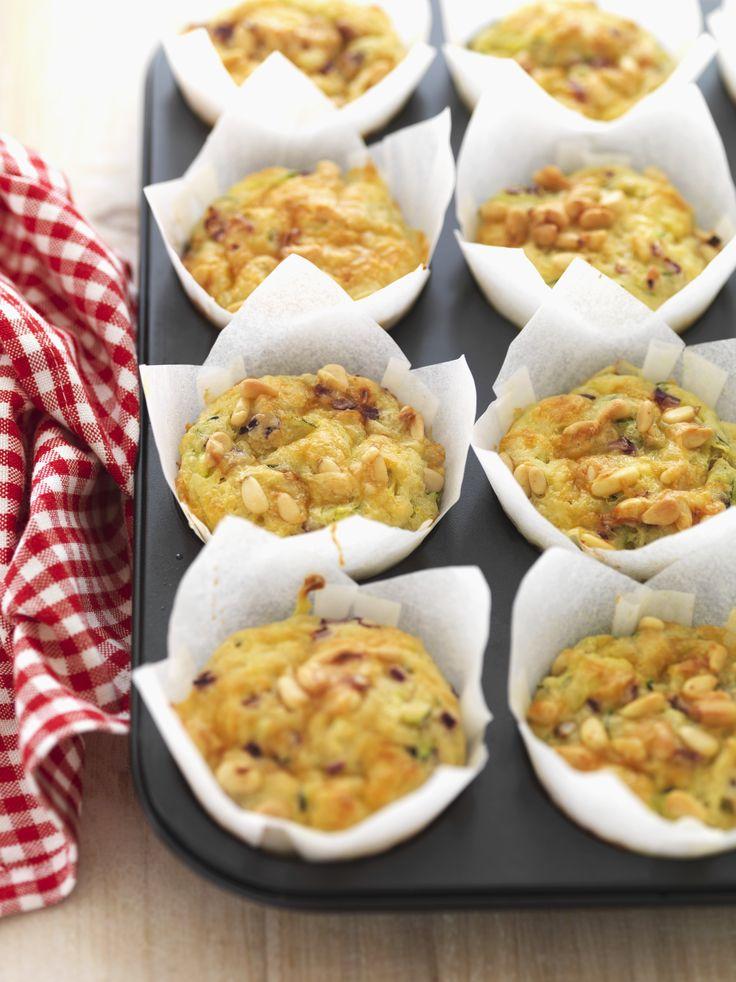 I muffin alle zucchine sono delle tortine salate adatte come antipasto: unite all'impasto cubetti di scamorza, parmigiano grattugiato e pinoli.