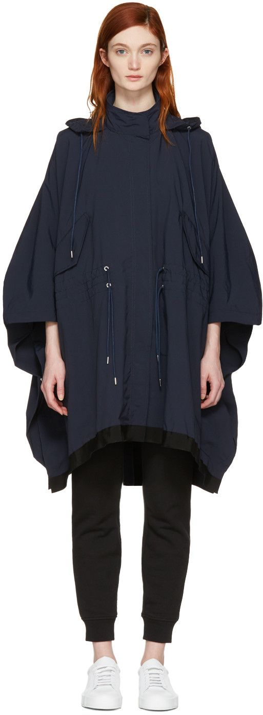 Long sleeve poncho in navy. Oversized fit. Stowaway hood at stand collar. Press-stud placket concealing two-way zip closure at front. Flap pockets and drawstring fastening at waist. Grosgrain trim in black at hem. Embroidered logo patch at side. Press-stud fastening at sides. Vented back hem. Silver-tone hardware. Tonal stitching.