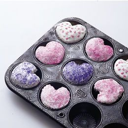 Cupcakes for Cupid ~ to create the heart shape, place a small marble or a 1/2-inch ball of aluminum foil between each liner and one side of the tin, this will push the paper into the batter to form the notch in the heart.