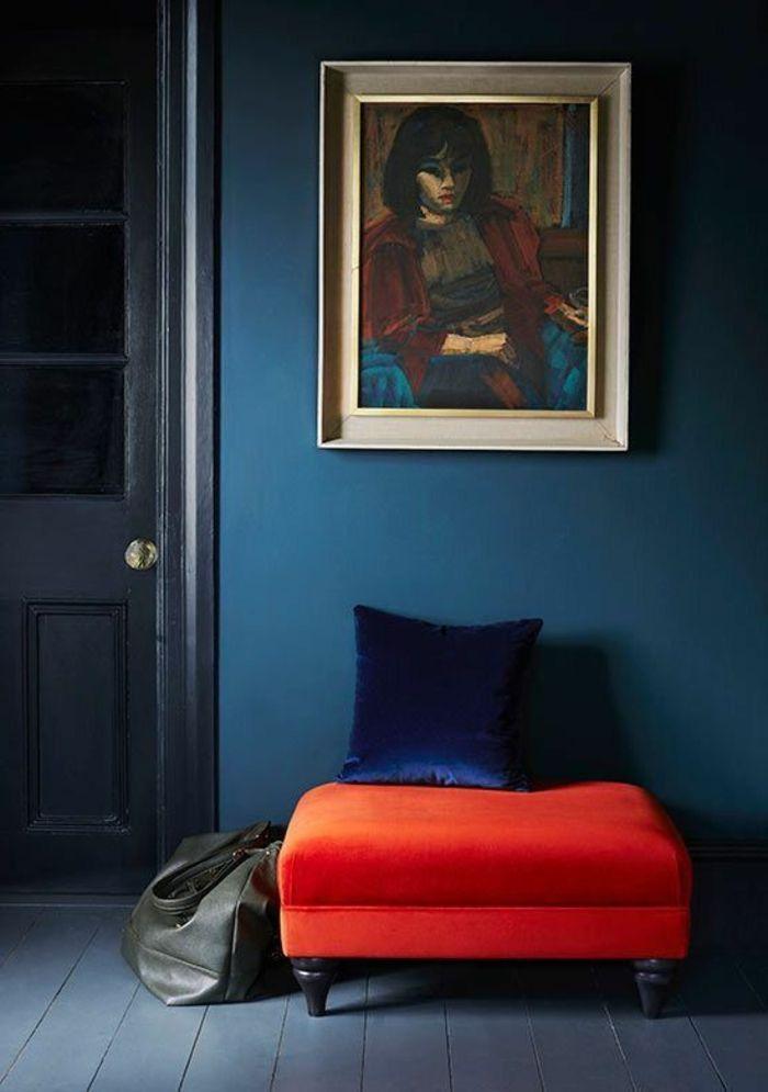 mur bleu canard, portrait de femme, tabouret rouge et coussin bleu