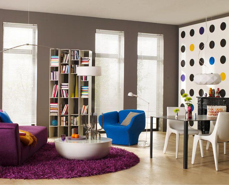 Sala moderna, com paredes cinza, móveis modernos e detalhes coloridos.