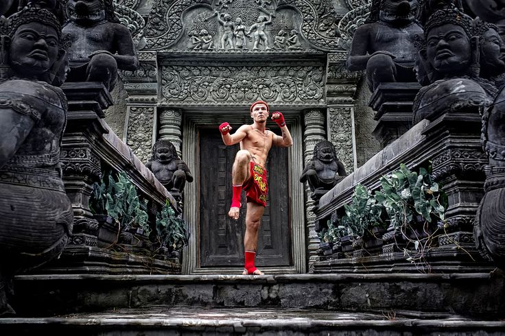 Muay Thai boxer posing outside temple