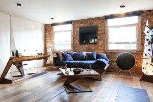 Eine rustikal aussehende Backsteinmauer gepaart mit rustikalen Holzboden verleiht diesem weiß gestrichenes Wohnzimmer einige Charakter. Foto: Nathalie Priem Photography