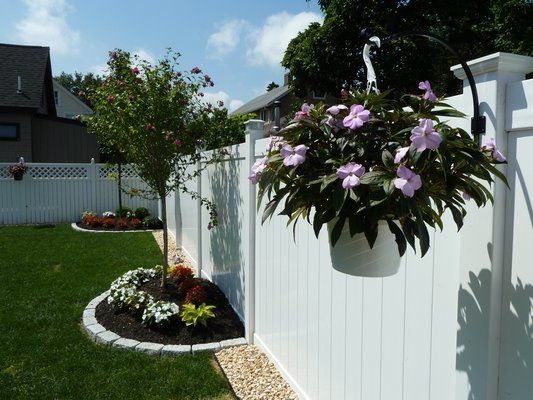 Privacy fence landscaping: pebble border = no trimming grass along fence!  And I love the post with potted plants.  Maybe some alternating with solar powered lights.  Also, take one corner with an extended  armed hook to place piñatas and stuffs at b-day bashes.