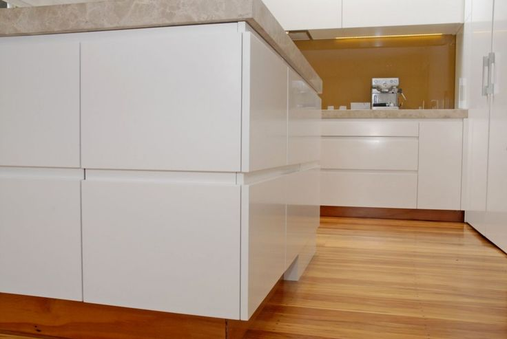 The contrast of white cabinetry with warm timber and warm toned glass splashback.