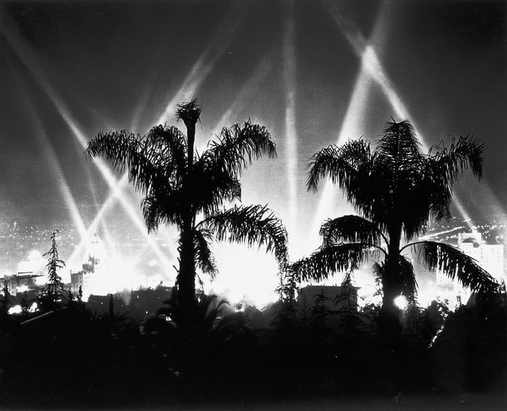 (1930)^ - Hollywood at night as seen from the Hollywood Hills. Spotlights can be seen in the background as Hollywood premiers another movie.