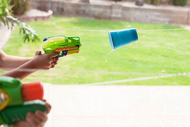 Use squirt guns to race plastic cups down a line. | 19 Backyard Water Games You Have To Play This Summer