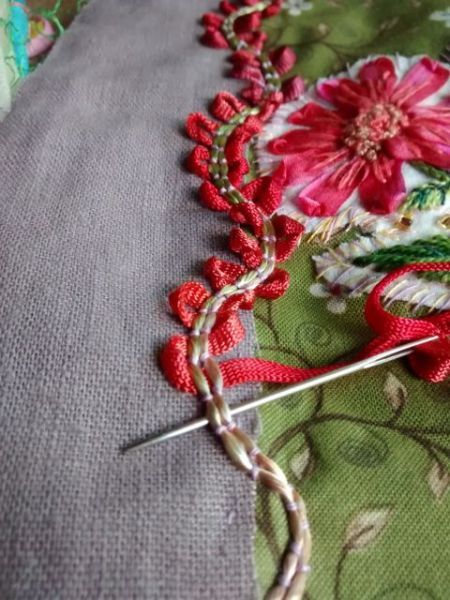 She threaded the ribbon through the couched stitches