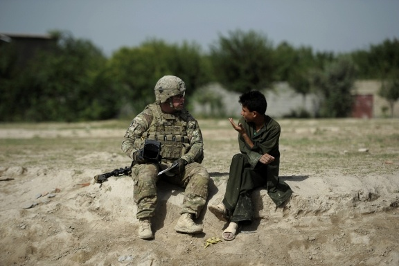 A U.S. soldier of the 501st Military Police Platoon speaks with an Afghan youth during a patrol in the village of Woro Keli, Buwri Tana district, in Khost Province on Aug. 7, 2012. (Photo by Jose Cabezas/Getty Images)