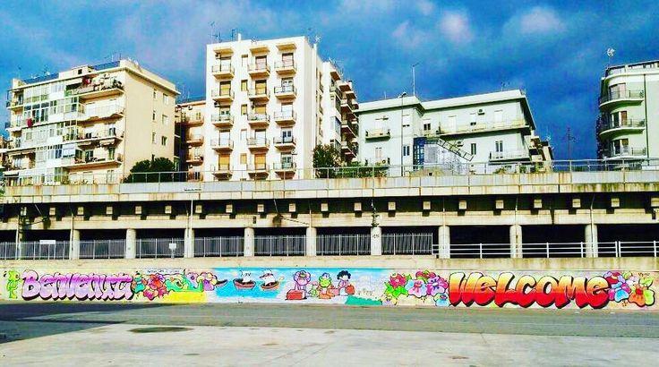 """Attraverso il murale realizzato gratuitamente dal parigino Nicolas Yosh abbiamo voluto rendere il Porto di Reggio Calabria un punto di approdo colorato e vivo per i turisti in arrivo in città oltreché più dignitoso per tutte le operazioni di accoglienza perchè """"...nessun uomo è un'isola!"""" I murales sono delle forme di arte che consentono la partecipazione e la rigenerazione urbana di luoghi spesso grigi e abbandonati. Per questo già nel 2016 abbiamo approvato un regolamento che disciplina la…"""